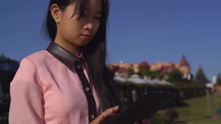 portrait attractive asian girl using touch screen tablet in the city. Beautiful adult woman send mail on modern device use 4g internet on the street. successful businesswoman wearing in elegant shirt