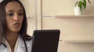 Portrait indian professional doctor has video online consultation with patient. Happy mixed race woman therapist wearing in white lab coat and phonendoscope sitting in office give advice about