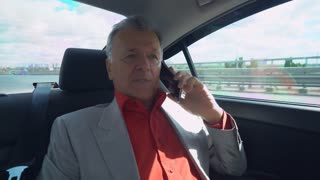Portrait middle age businessman sitting on the backseat in the car. aged man sits on a seat at the back of a vehicle using mobile phone. Happy male in years talking on the smartphone drive on the