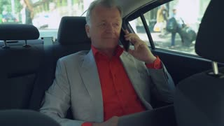 Portrait middle aged man talking on the smartphone. Professional businessman in years wearing in elegant suit speaking on the mobile phone driving on car. Male sitting on the back seat smiling with