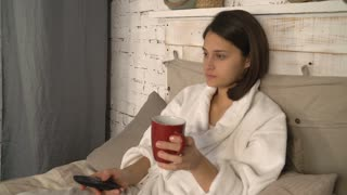 Portrait woman drinking tea or coffee. Young lady lying in bed wearing in white bathrobe change channel with tv remote. Smiling girl watching comedy show at home