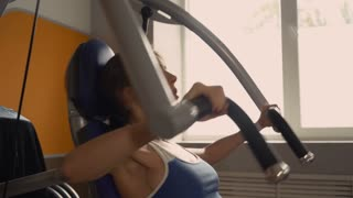 Portrait woman in the gym. Female pumping muscles hands and chest on training machine near the window with sunshine. Happy woman enjoy exercises. Sporty girl doing morning workout with weight-lifting