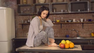 Portrait woman with apple. Happy girl eating fresh fruit in kitchen. Caucasian brunette sitting on the table near her dish with fruits. Beautiful lady wearing in sleepwear barefoot in the morning in