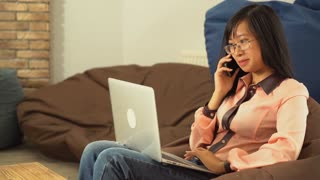 Portrait young asian woman talking on the smartphone using computer. Happy smiling businesswoman answer call with smile. Girl sitting on the chair in the room search some information on laptop using