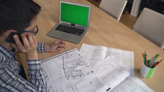 Professional designer speak with customer on the smartphone looking on the architectural sketch. Young man sitting at the working place in design agency. Laptop plan blueprint plan pencil equipment