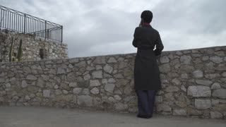 Rear back view. Looking on the cityscape. Business wearing in elegant grey long coat. Cloudy day in autumn season