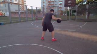 Rear back view man plays basketball urban view. Active lifestyle summer season