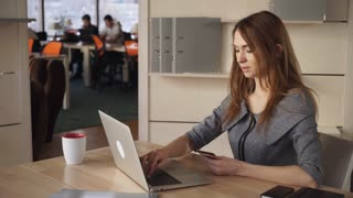 Red-haired adult woman at the office odering on laptop some goods. She holding orange debit card and shopping at the internet shop