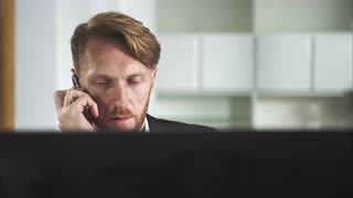 Red-haired man sitting at a computer and calling on the phone. UHD