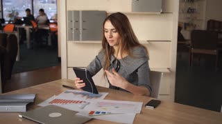 Red- haired woman has conversation with business partner. She using video call on the tablet. Female at the light office. On her wooden big desk financial report chart graph and colored diagram
