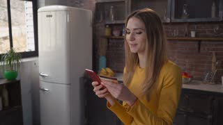 Redhead lady holding smartphone and creditcard. Smiling blonde woman entering security code shopping online at home. Portrait adult lady in the kitchen using mobile phone pay via internet