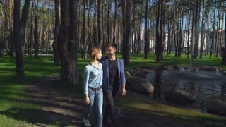 Romantic date in the park with beautiful lake. Happy couple in love walking and talking. Caucasian man and woman spend free time outdoors. Attractive young couple wearing in casual dress female denim
