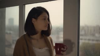 Sad and calm lady with brown hair wrapping up in plaid. Woman looking out the window in autumn season rainy day at home. Lady drinking tea or coffee hold red mug