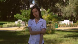 Sad asian woman in the park. Beautiful female stands on the street in summer season wearing in white shirt takes thought or sadden about something. Young businesswoman with long black hair wearing in