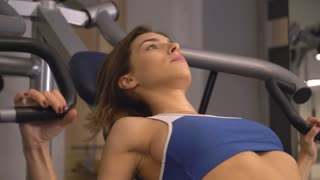 shapely bodybuilder practice alone in gym. Woman doing exercises on biceps training machine in sport club or at home. athlete with fair hair wearing in blue sport top