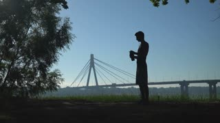Silhouette of athletic young male standing hectares of lawn with sand and drinking from a bottle outdoor near the tree. In the background bridge with car. Man drinks water after workout. Healthy sport