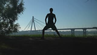 silhouette runner warming up muscles legs before running. Urban city view in sunset. On the bridge over river riding cars and different vehicles