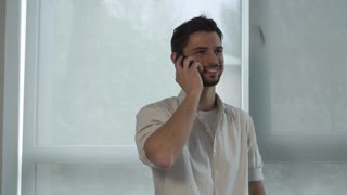 Smile male using smartphone. Casual young guy wearing in shirt talking on mobile. Mixed race model