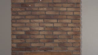 Smiling cute schoolboy walking along brick wall at the table with writing on flip chart start up