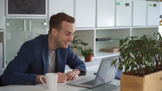 Successful businessman using app on computer for remote meeting. Handsome caucasian male talking emotionally with client and smiling. Professional worker or head department consult with financial