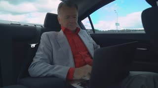 Successful elderly businessman typing on computer rides in car on the meeting. Old - aged boss computing or surfing internet or working with documents on the way to work wearing in elegant suit and