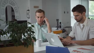 Teamwork professional men in the startup company. Caucasian handsome man talking on the smartphone. Mixed race male typing on the computer. On the table financial documents with diagrams charts