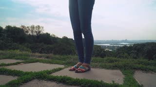 The young beautiful stylish girl with long hair in bright blue pants and sandals, standing on a hill and gaining a message on the phone. Over the hill rising above the church and the river