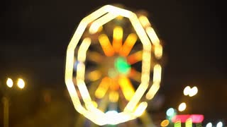 Theme park at night. Defocused spinning LED lit attraction. 4K background bokeh shot