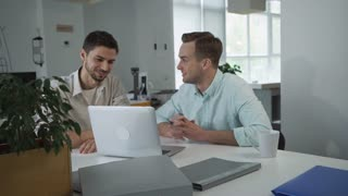 They sitting together at the workplace looking something funny on the computer and laughing.  Male has break at the work. Young men working in a light and modern office