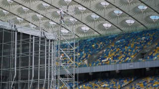 Three workers lifted up the rope, standing in a construction ladder on the big stadium with blue and yellow seats
