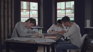Three young casual co workers sitting at the wooden desk in modern contemporary office with big windows. Caucasian employees handwriting filling paper documents. Colleagues in start up company woman