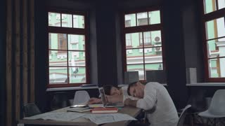 tired employees fall asleep at work. Young businessman and business woman sleeping at the working place. Happy smiling man associate entering into the room and bring coffee. Handsome workers holding