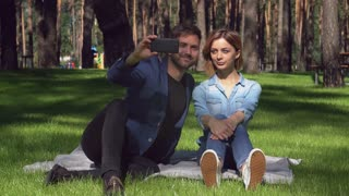 Tired woman and smiling man sitting on the grass take selfie photo at the park. Beautiful couple in love have fun on a date. Casual girlfriend and boyfriend in sunny summer day. Happy people wearing
