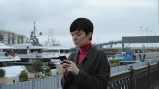 Tourist use 4g on mobile phone in harbour. Female in autumn season wearing in casual coat. On the background people on yacht and boats