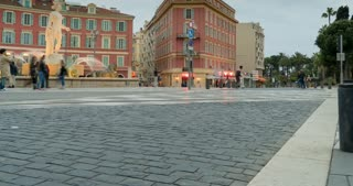 town square in nice france. People cross the road at traffic signal. fountain in historic center. tram rides in the evening. time lapse