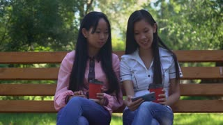 Two asian friends drinking coffee to go and watching funny video on smartphone. Laughing businesswoman or students sitting on the bench. Girls holding red paper cup in hands. Smiling woman using