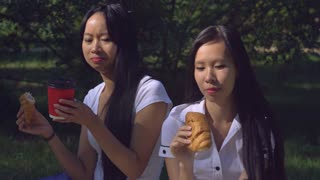 Two friends eating breakfast in the park. Happy women eat croissant outdoors. Girls meeting have conversation smiling enjoy bake at the open air