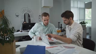 Two handsome office worker working in the open space room. On the table folder with documents and diagrams. Business meeting of two men for brainstorming