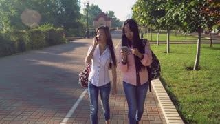 Two happy smiling girls going on pavement use smartphone. Vietnamese girl talking on mobile phone and laughing. Young woman texting message or chatting or looking map in application search right