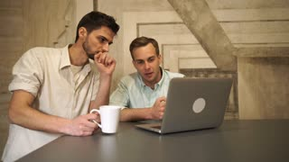 Two men discussing future project. Pair of happy workers with computer communicate. Handsome caucasian man and mixed race male laughing and chat. On the modern table white cup with drink