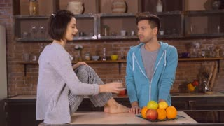 Two people drinking clear water in the kitchen. Man and woman have fun at home. Adult man looking with love on his lover. Attractive woman sitting on the table wearing in sleepwear