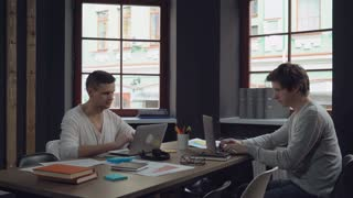 Two young businessmen working in the modern contemporary office with big windows. Group of people works with computer sitting at the wooden desk with paper documents. Happy startup team