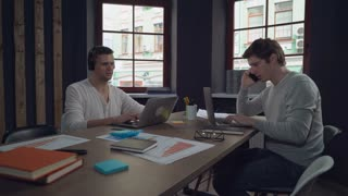 Two young man working in the office. Handsome caucasian man talking on the smartphone. guy with black hair listening music in headphones sitting at the working place using laptop. Startup team use