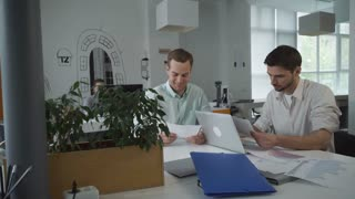 Using computer for working with marketing financial report. Informal casual business meeting for brainstorming