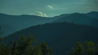 A beautiful panorama timelapse of wood hills with curly moving clounds and shaking trees in front. The sun rays dance above the forests during the videoshot. The sight is stunning