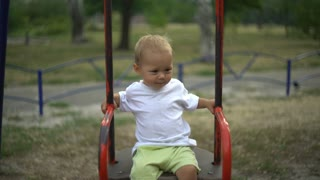 A cute toddler is sitting on the swing, alone. The child has blond hair and swaying and smiling. He is happy and cheerful. The kid has a white T-shirt, yellow shorts and sandals
