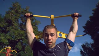 A fit sporty guy is making pull ups during the video. His muscles are evident in the clip. The male is listening to music in his headphones and is working out outsise