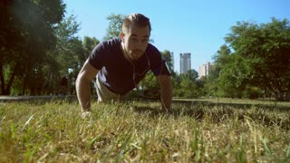 A handsome man in trendy outfit makes push ups during the video. He is wearing a blue T-shirt and an armband for the smartphone. The male is working out in the park with an urban background