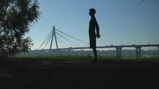 A sporty man is working out. He is holding his hands back in a lock and raises them up and down to stretch. He is training in the park with a beautiful city scale on the background
