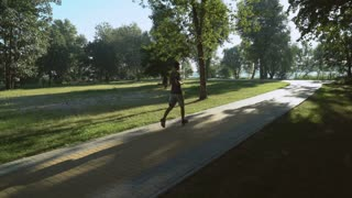 A young man is running forward along the path (backview). A male is wearing casual sports outfit and he is training out in the nature. An urban background of a park surrounds the person